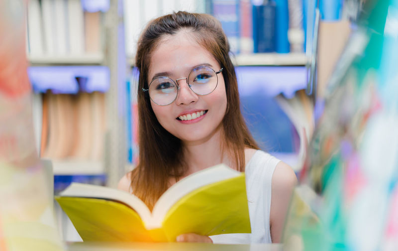Close-up portrait of young woman studying in library