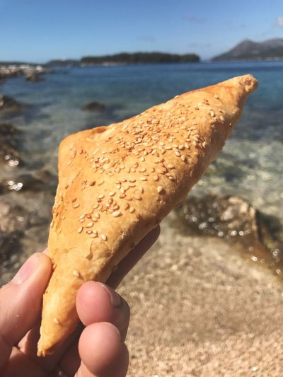 EyeEm Selects Croatian cheese strudel Human Hand Human Body Part Food And Drink Human Finger Holding One Person Food Focus On Foreground Close-up Real People Indulgence Freshness Sweet Food Day Outdoors Ready-to-eat Temptation Unhealthy Eating Beach Water Strudel Cheese Strudel Croatia Dubrovnik