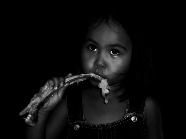 Take A Bite EyeEm Best Shots EyeEm Selects EyeEm Nature Lover Eyeem Philippines Sony Xperia Photography. Sony Xperia Z3 EyeEm Gallery EyeEmBestPics EyeEmNewHere Black And White Photography Portrait Child Childhood Looking At Camera Headshot Black Background Holding Close-up Biting Children Hungry Non-profit Organization