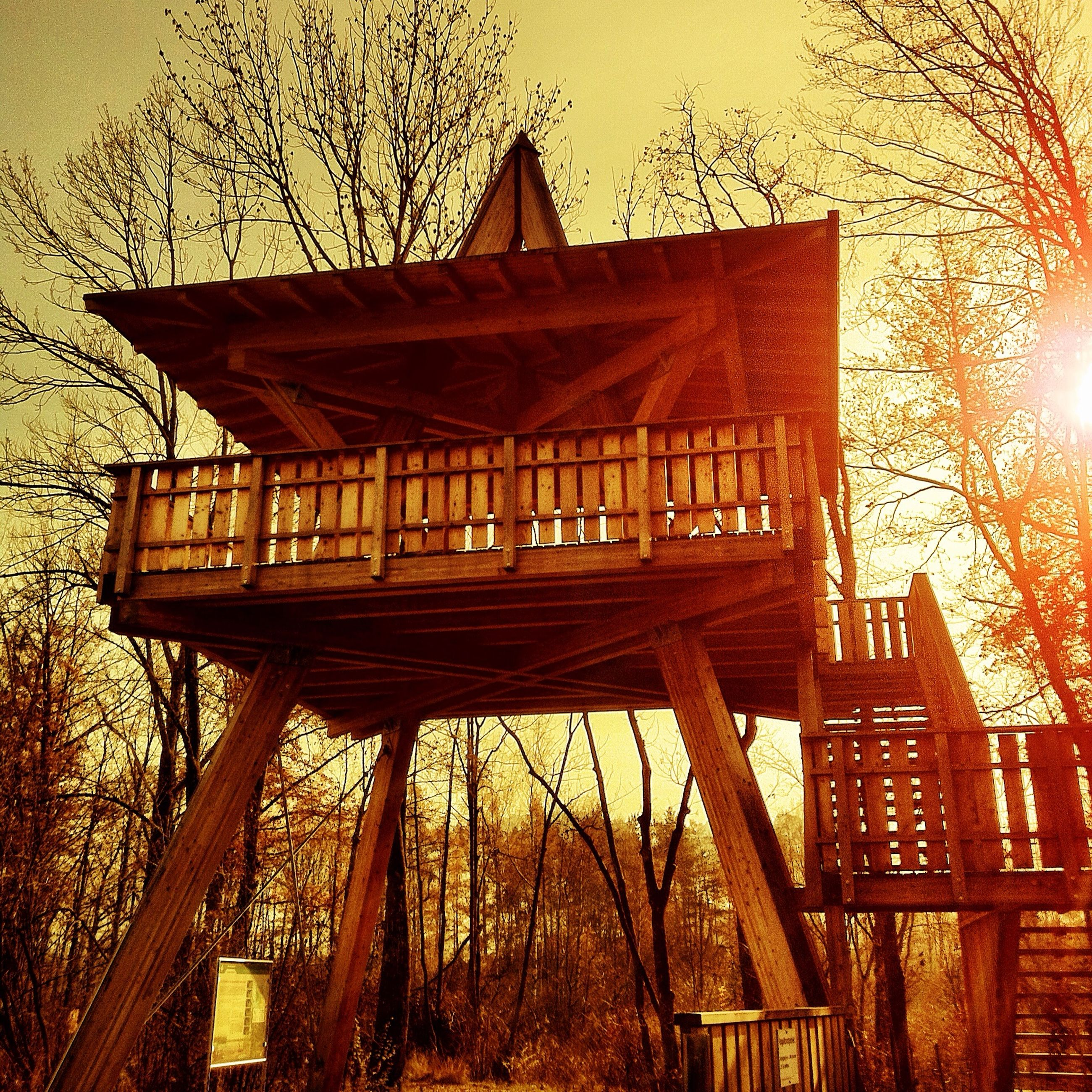 built structure, architecture, building exterior, tree, house, wood - material, low angle view, sunset, bare tree, sky, outdoors, no people, branch, sunlight, clear sky, residential structure, orange color, exterior, nature, day
