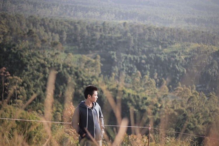 Young man standing on field against trees