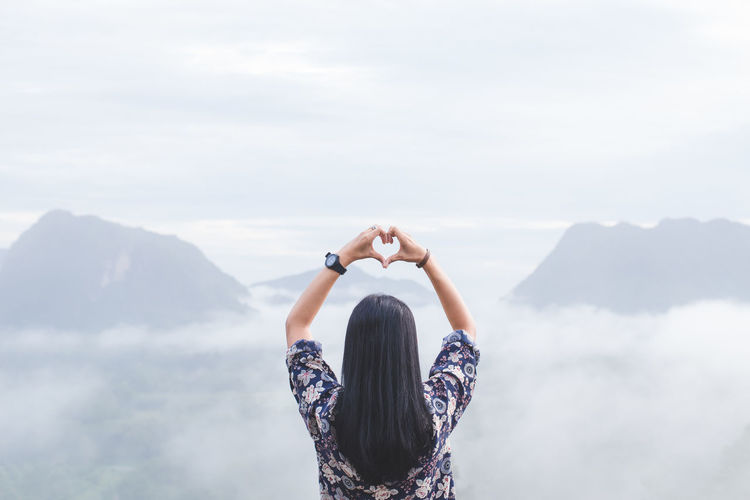 Rear view of woman making heart shape while looking at mountains