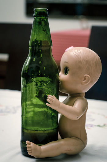 Close-Up Of Alcoholic Drink In Bottle By Doll On Table