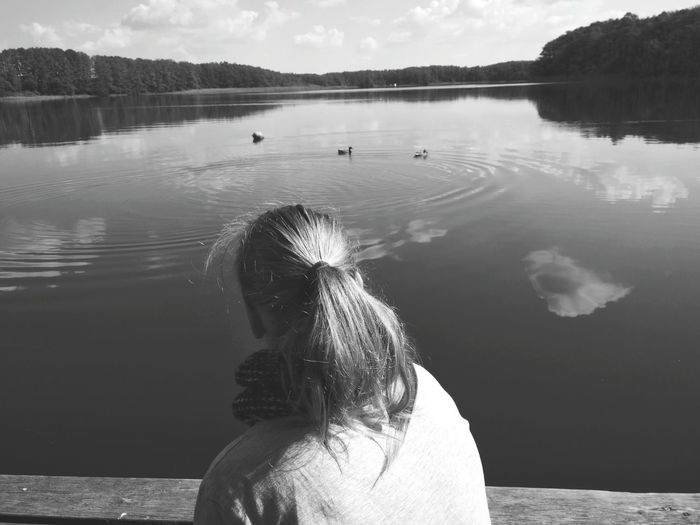 Woman looking at view against lake during sunny day