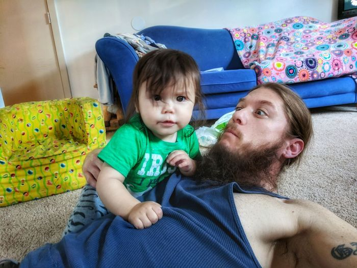 Portrait of baby boy with father lying at home