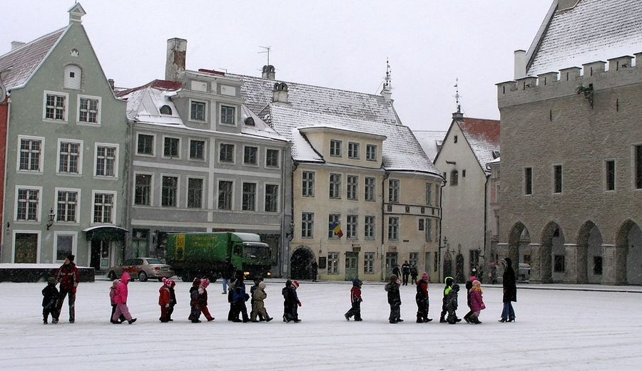 People on street against buildings in city during winter