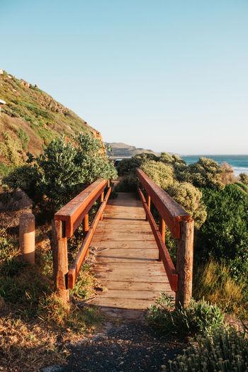 Wooden footbridge leading towards sea against clear sky