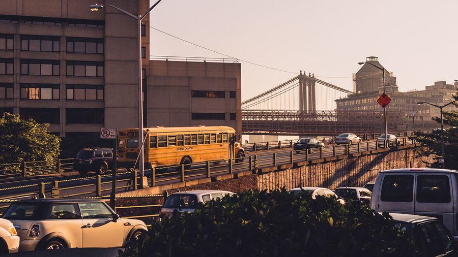 Vehicles on road against manhattan bridge in city