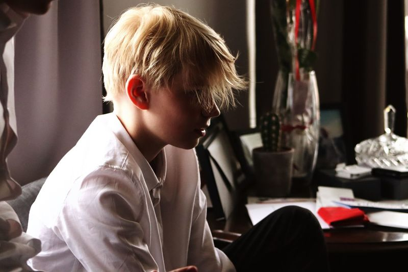 Thoughtful boy sitting on sofa at home
