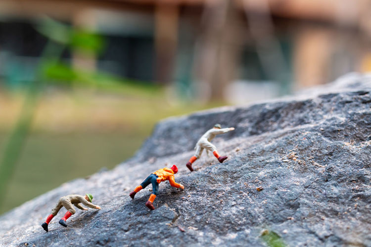 Miniature hikers climbing up on the rock