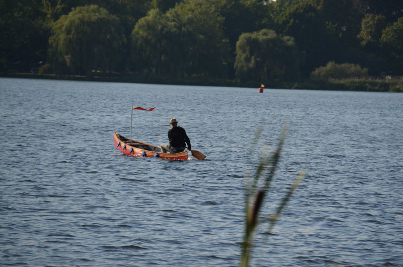 Rear view of man rowing boat in river