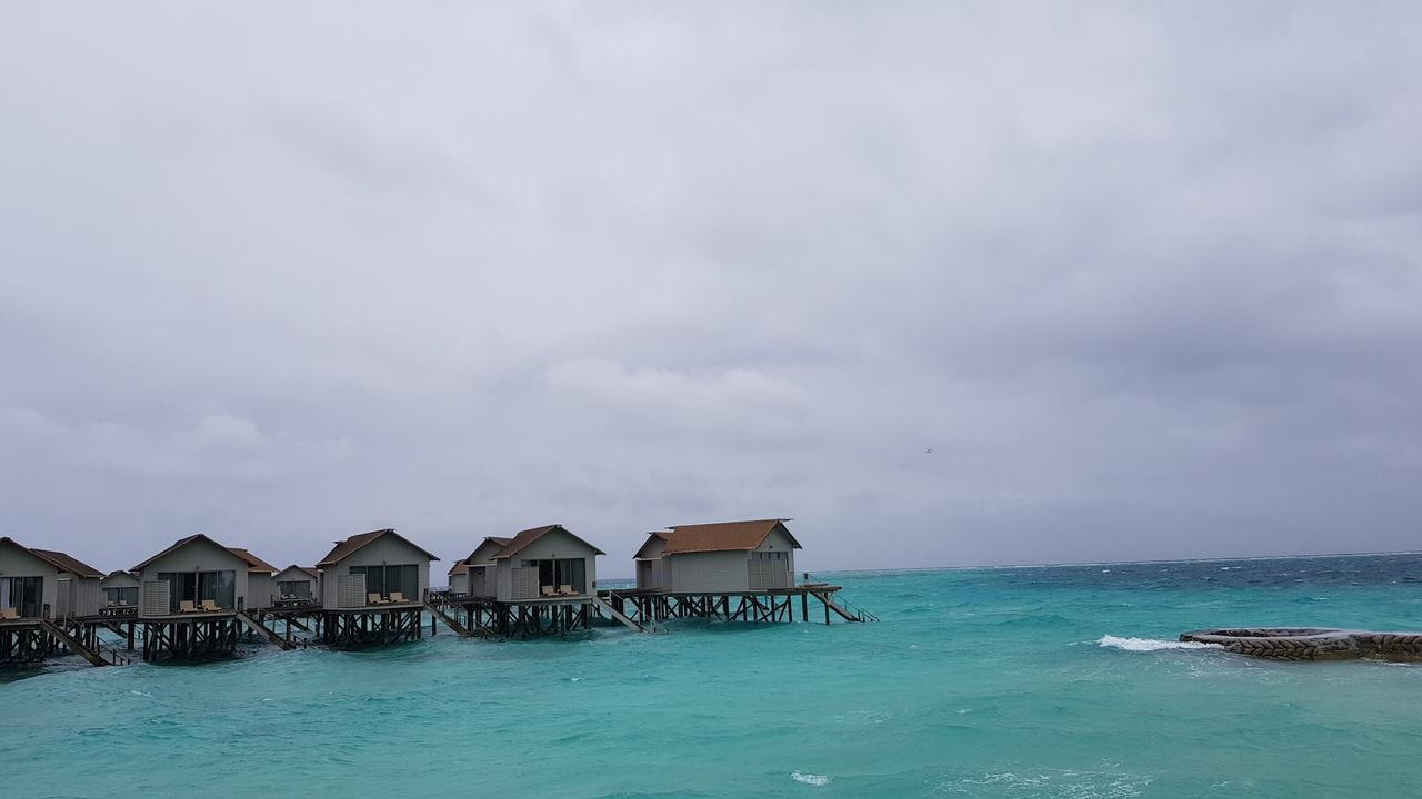 HOUSES ON SEA AGAINST SKY