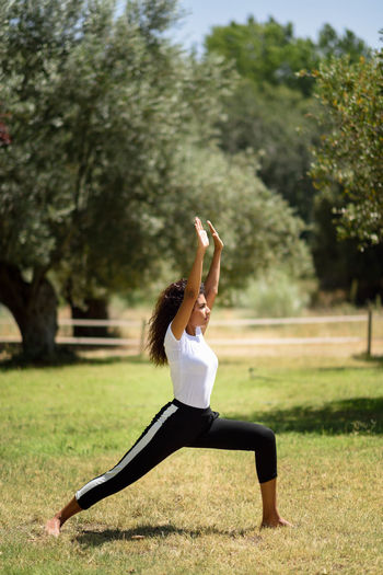 Full Length Of Young Woman Practicing Yoga In Warrior Position At Park