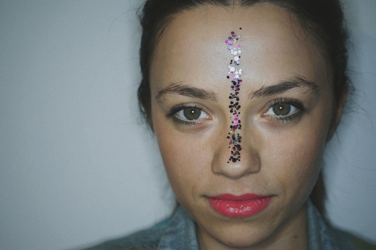 Portrait of beautiful young woman with sequins on face against wall