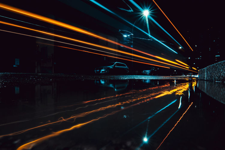 Light trails on bridge over river in city at night