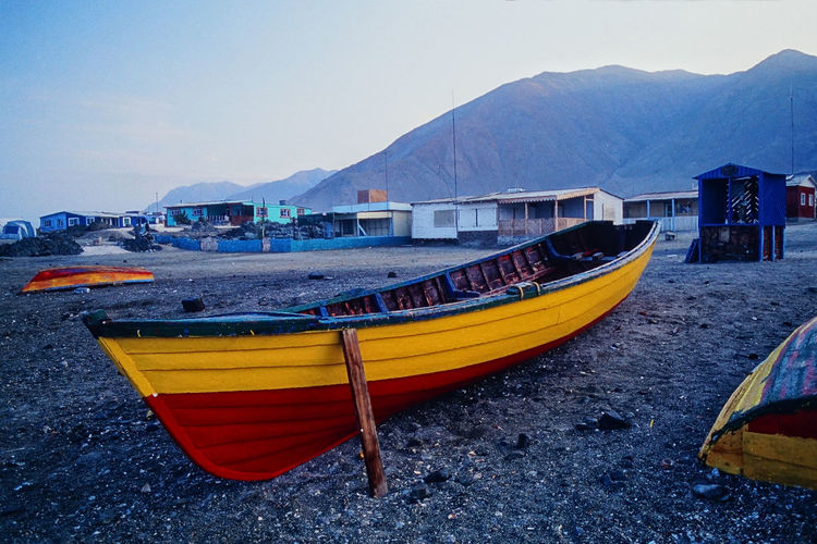Boats moored on sea by mountain against sky