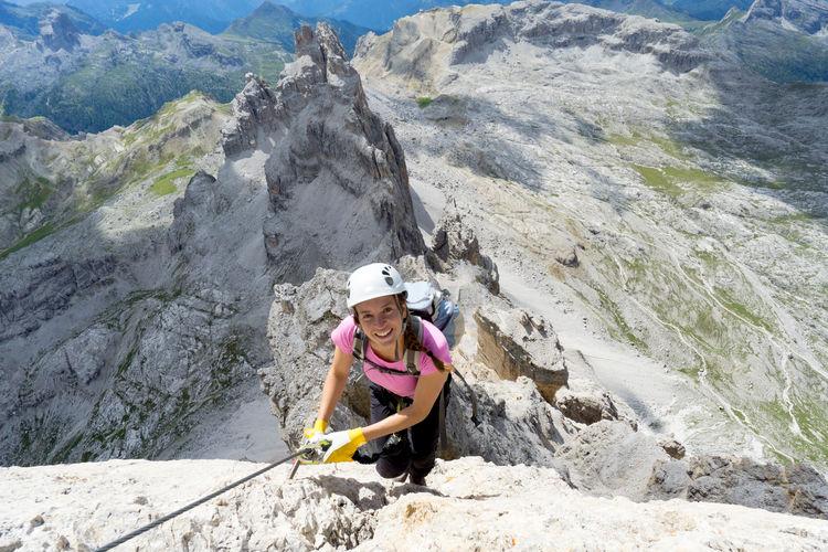 High angle portrait of woman climbing rock