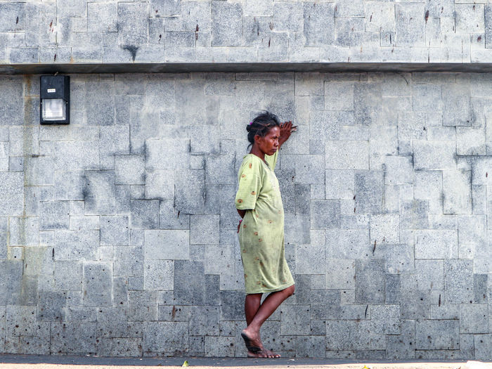 Side View Full Length Of Homeless Woman Standing By Wall
