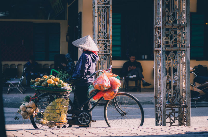 Waiting ... Architecture Asian Style Conical Hat Bicycle Building Exterior Built Structure Day Full Length Hat Lifestyles Mammal Men Occupation One Person Outdoors Real People Transportation Women