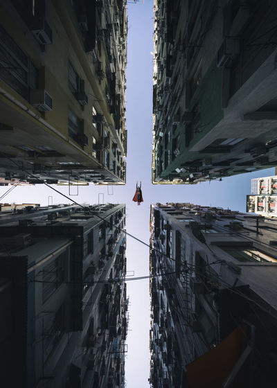 Directly below shot of superman flying amidst buildings in city