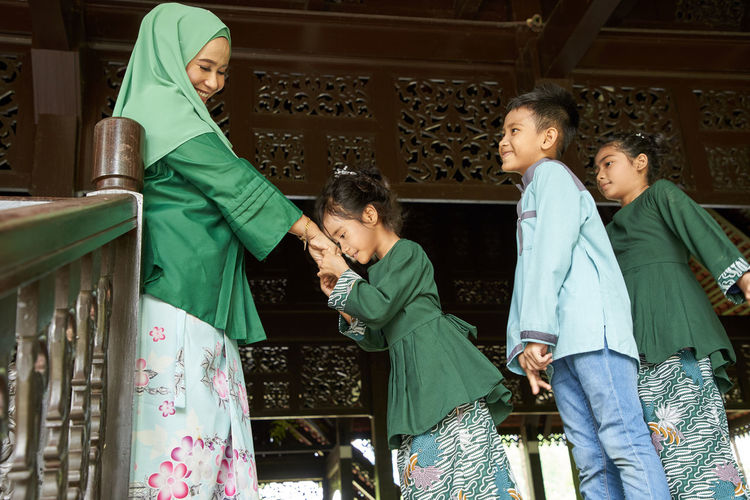 Daughter and son standing in a row greeting mother ask forgiveness during ramadan festival