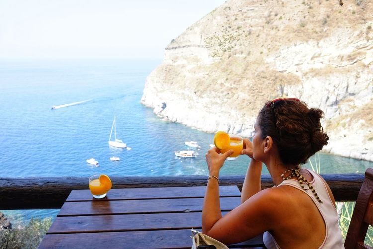 Side View Of Woman Holding Orange Juice While Looking At Sea From Restaurant