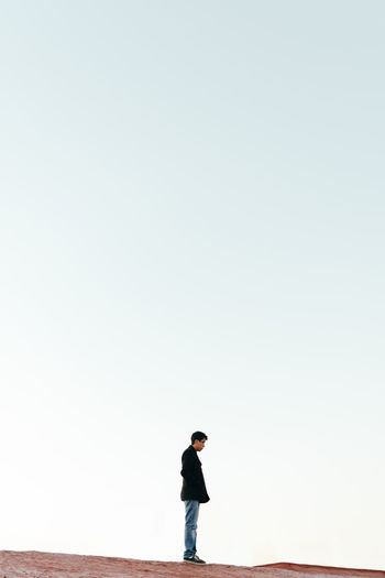 Full length of man standing on rock against clear sky