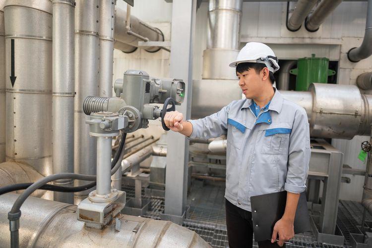 Worker examining equipment in factory