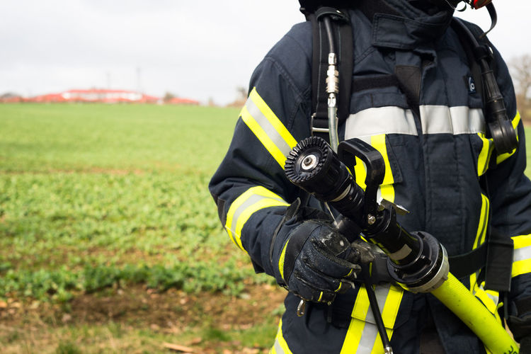 Midsection Of Firefighter Standing On Field