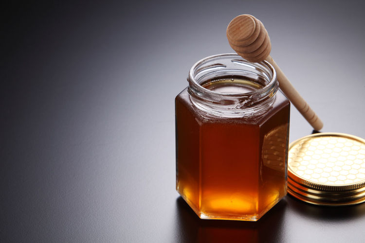 Close-up of honey in jar on gray background