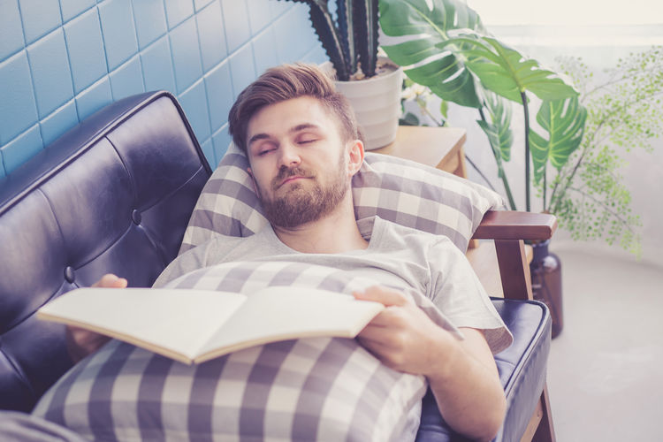 Young Adult One Person Relaxation Young Men Lifestyles Real People Furniture Sitting Front View Indoors  Men Reading Publication Book Leisure Activity Lying Down Sofa Beard Armchair Contemplation