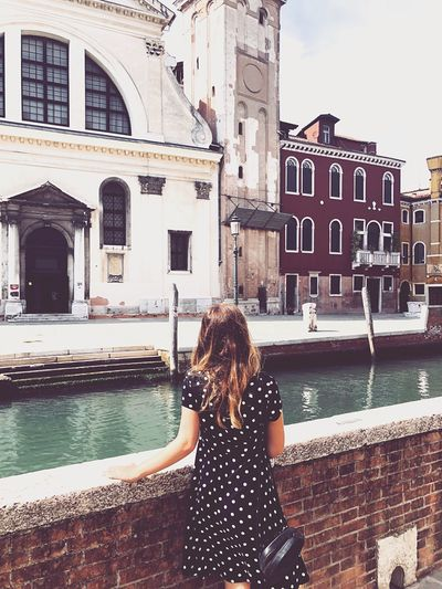 Rear view of woman standing by canal in city