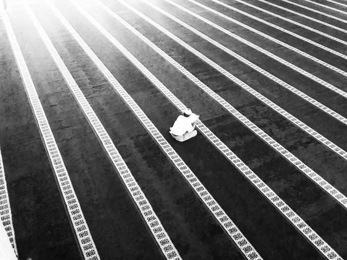High Angle View Of Man Praying On Striped Flooring Outside Mosque