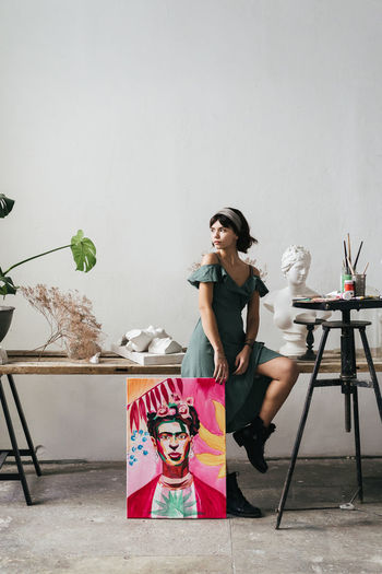 Female artist sitting painting and bust at art studio