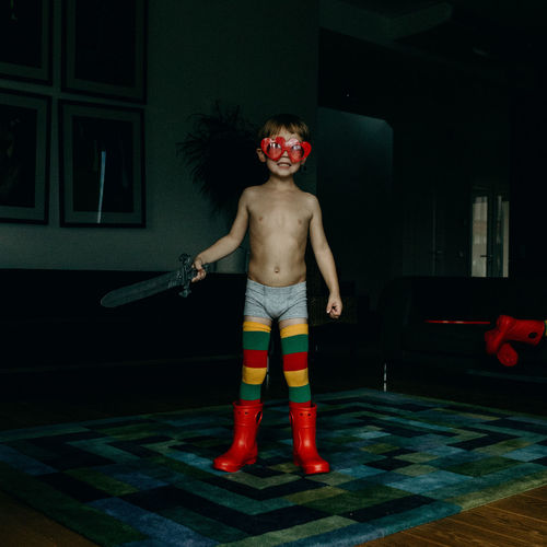 Full length of shirtless boy playing with sword toy at home