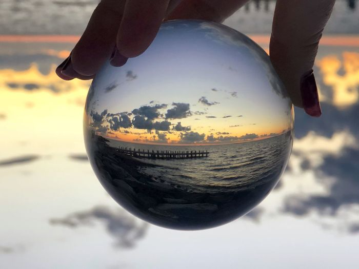 Beauty In Nature Nature Nature Photography Taking Pictures Taking Photos Abstract Sunrise Sunset Circle Shape Reflection Lensball Nature Sky Close-up Reflection Focus On Foreground One Person Beach Human Body Part Human Hand Hand Cloud - Sky Sunlight Holding Day Sphere Sand Outdoors Water