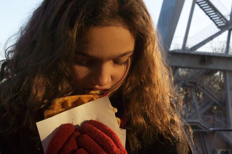 Close-up of girl eating waffle