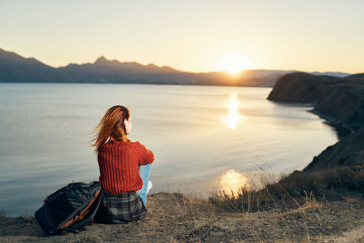 Woman sitting on shore against sky during sunset