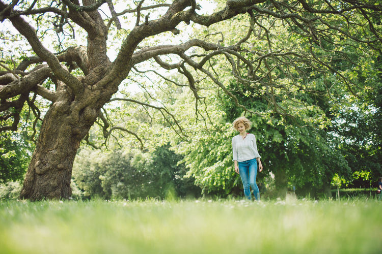 Full length of mid adult woman walking against tree in field