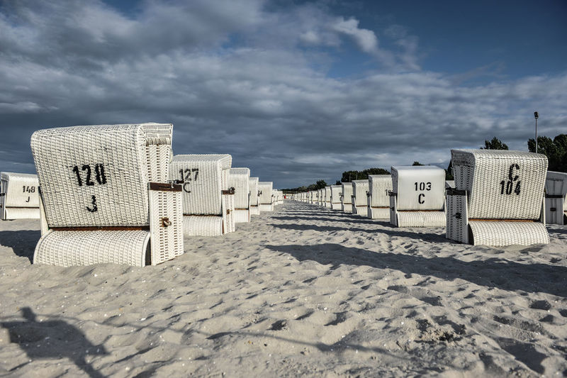 Lounges on sand against sky