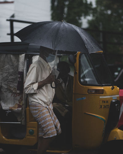 Rear view of a man with umbrella