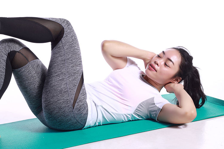Young Woman Exercising On Mat Against White Background