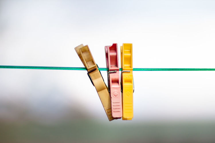 Close-Up Of Colorful Clothespins On Clothesline Against Sky