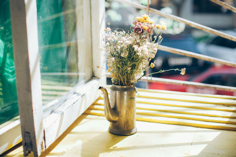 Flowers in container on window sill