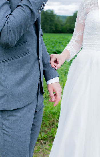 Midsection Of Bride And Groom Standing On Field