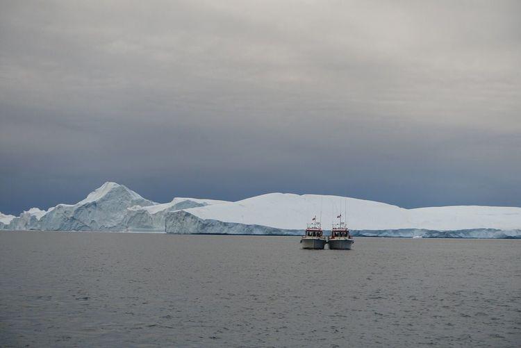 Boats on sea against icebergs