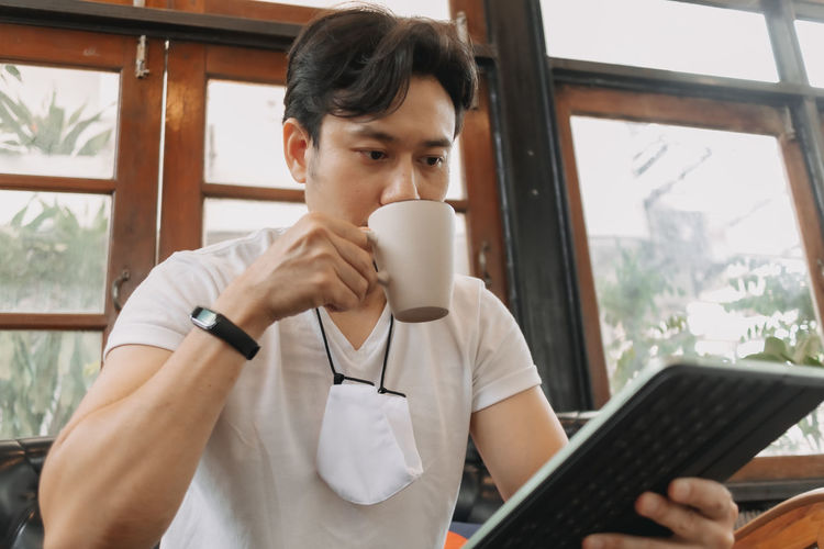 Mid section of man holding coffee cup at home