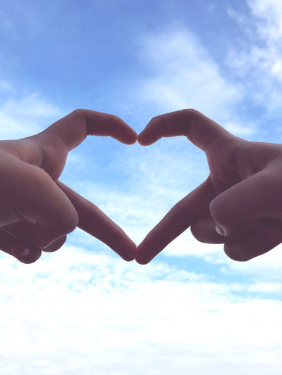 Close-up of hand holding heart shape against sky