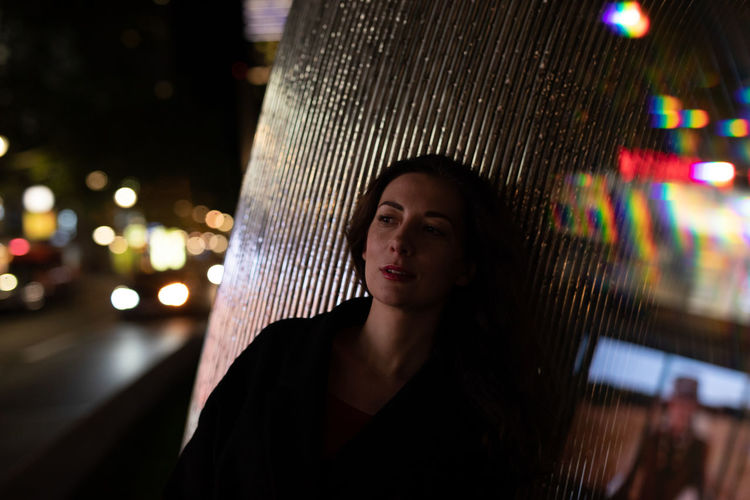 Mid adult woman leaning on pillar in city