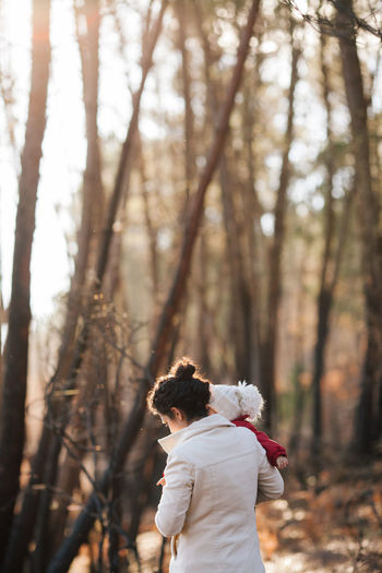 Rear View Of Mother Carrying Baby Girl Standing Against Trees At Forest